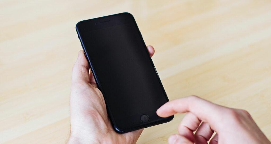 pessoa segurando celular iphone preto desligado