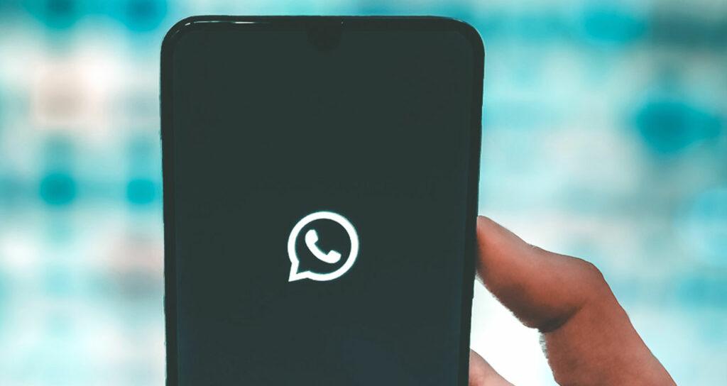 pessoa desligando celular com logo whatsapp