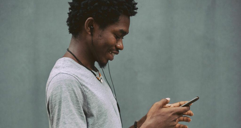 homem feliz com celular na mão